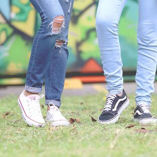legs of 2 young people standing together