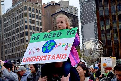 Little girl holding sign to protect environment 3 2 .jpg