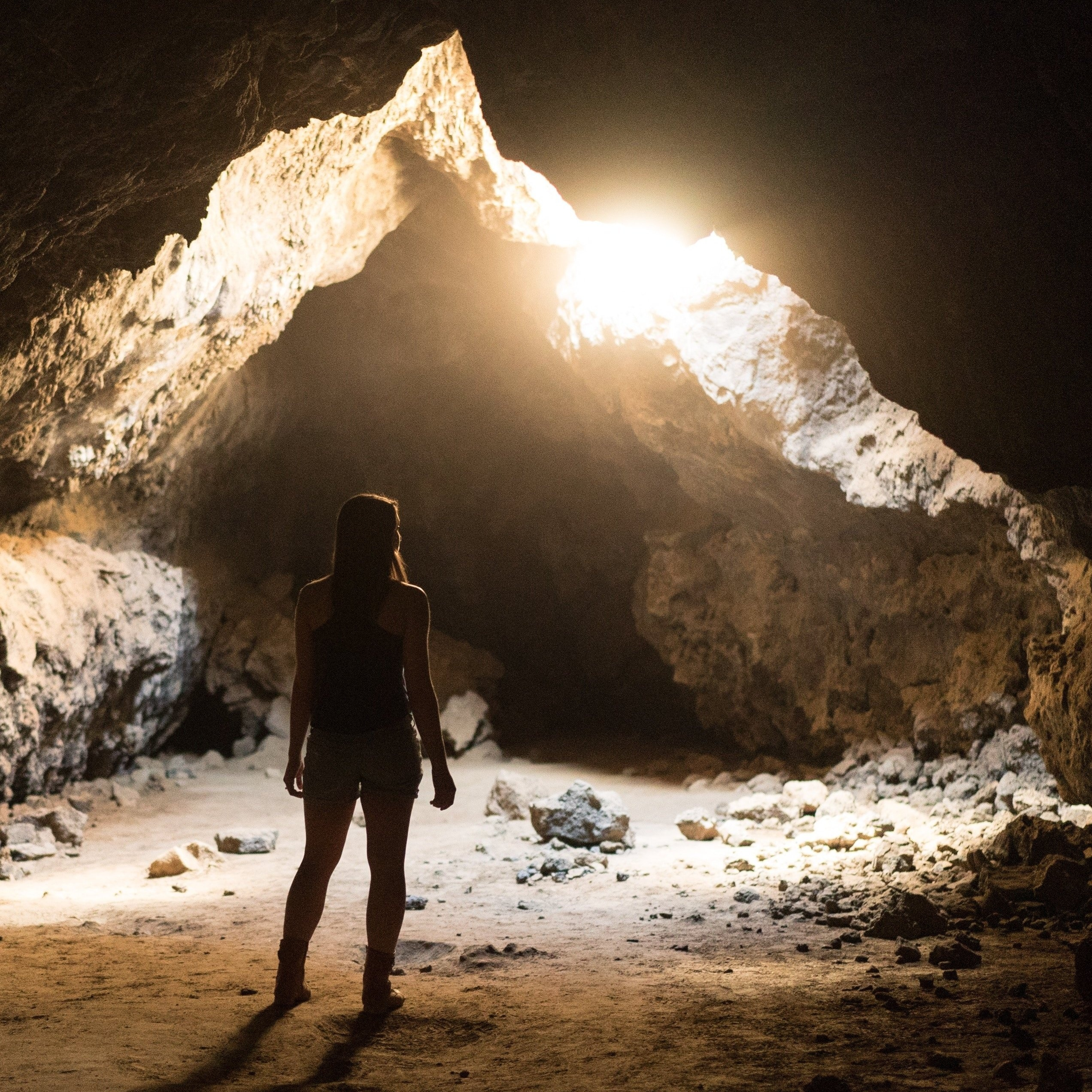 Woman standing in cave looking towards light