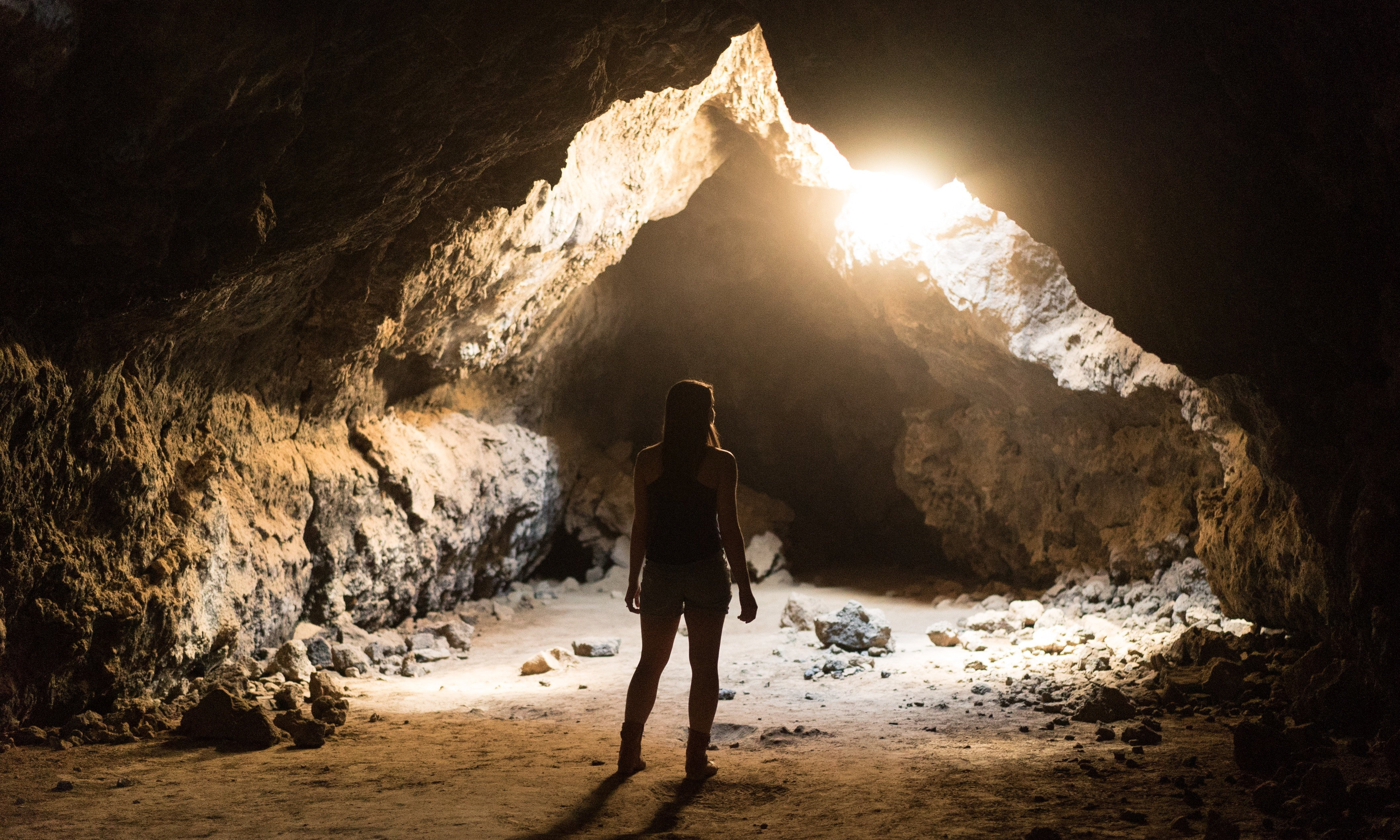 girl staring into sunlight cave
