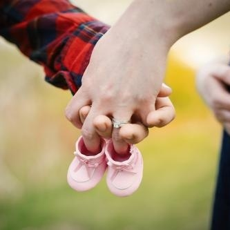 couple holding hands with baby shoe