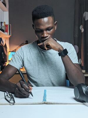 photo-of-man-writing-on-notebook