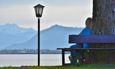 woman sitting on bench with mountains-465171-edited