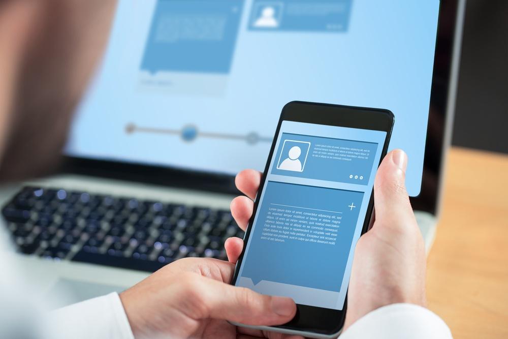 Businessman using smartphone against website interface.jpeg