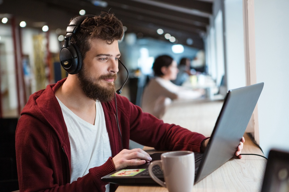 Concentrated handsome male with beard using headset and laptop.jpeg