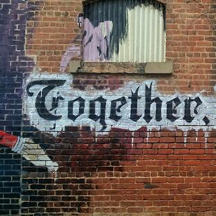 brick wall with together written across
