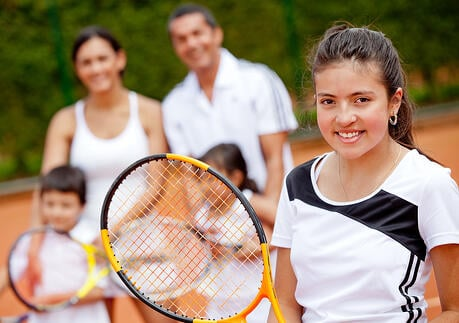 Young female tennis player with her family at the background