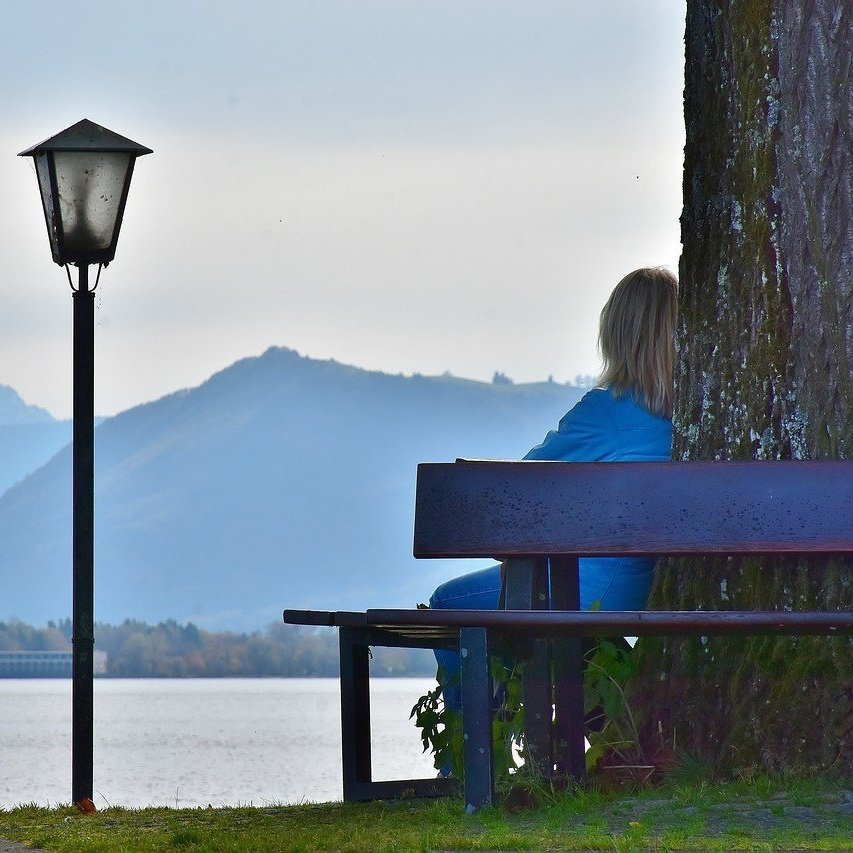 woman sitting on bench with mountains square.jpg