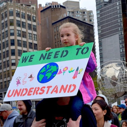 Little girl holding sign to protect environment